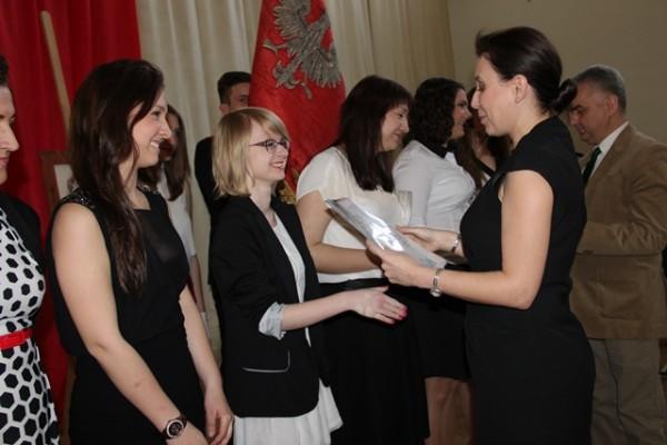 Pani Wicedyrektor Barbara Kalinowska wręcza listy gratulacyjne uczniom kl. III d